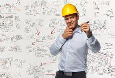 Trabalhador masculino de sorriso no tampão duro amarelo que guarda uma pena Foto de Stock Royalty Free