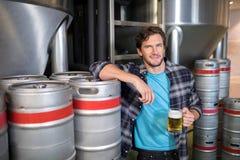 trabalhador masculino de sorriso que guarda o vidro de cerveja ao estar na fábrica imagens de stock