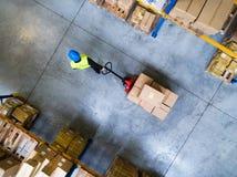 Trabalhador masculino do armazém que puxa um caminhão de pálete foto de stock