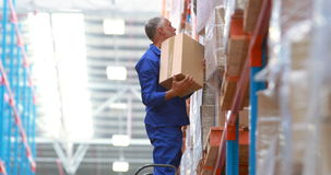 Trabalhador masculino do armazém que usa a escada para arranjar a caixa de cartão video estoque