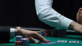 Trabalhador masculino do casino que negociam cartões e jogador que verifica suas mão, sorte e fortuna video estoque