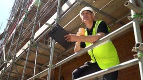 Trabalhador masculino do contramestre do construtor na posição do terreno de construção da construção na escrita do andaime na pr filme