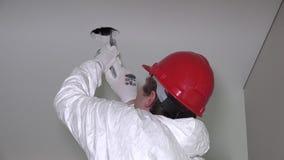 Trabalhador masculino especializado que faz furos do teto do drywall para a instalação de iluminação video estoque