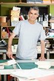 Trabalhador masculino maduro seguro que está na tabela Fotos de Stock