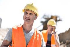 Trabalhador masculino no canteiro de obras com o colega que está no fundo Foto de Stock Royalty Free