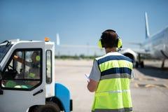 Trabalhador masculino nos fones de ouvido que olham aviões quando sócio que senta-se no veículo imagens de stock royalty free