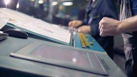 Trabalhador masculino que usa o écran sensível do computador digital ao lado da linha de produção na fábrica vídeos de arquivo