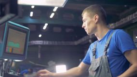 Trabalhador masculino que usa o écran sensível do computador digital em uma linha de produção da fábrica filme