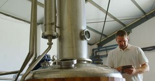 Trabalhador masculino que usa a tabuleta digital ao examinar o tanque 4k da destilação filme