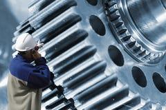 Trabalhador, mecânico com engrenagens gigantes e rodas denteadas fotografia de stock royalty free