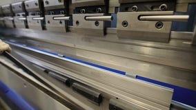 Trabalhador na fábrica na máquina da faixa clara do metal que põe a parte do trabalho dentro Homem que trabalha com chapa metálic video estoque