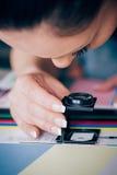 Trabalhador na impressão e em usos centar da imprensa uma lupa foto de stock