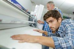 Trabalhador na linha de revestimento máquina da imprensa do cargo fotografia de stock