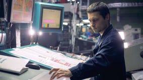 Trabalhador na máquina automatizada industrial que opera-se com linha da fábrica video estoque