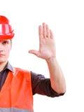 Trabalhador na mão da parada da exibição do capacete de segurança da veste da segurança Fotografia de Stock Royalty Free