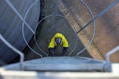 Trabalhador na máscara e uniforme que vai acima uma escada do metal Fotografia de Stock Royalty Free