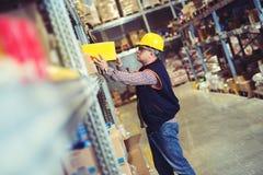 Trabalhador no armazém que prepara bens para a expedição foto de stock