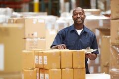 Trabalhador no armazém que prepara bens para a expedição fotos de stock royalty free