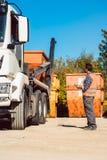 Trabalhador no canteiro de obras que descarrega o recipiente para o desperdício do caminhão Fotografia de Stock