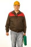 Trabalhador no capacete alaranjado protetor com uma mala de viagem verde Imagem de Stock Royalty Free