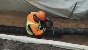 Trabalhador no capacete de segurança alaranjado que senta-se na paz da graxa da vala do tubo plástico preto vídeos de arquivo