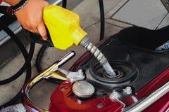 Trabalhador no posto de gasolina que enche-se acima da motocicleta dos clientes com o gasol fotos de stock