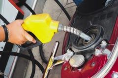 Trabalhador no posto de gasolina que enche-se acima da motocicleta dos clientes com o gasol fotografia de stock royalty free