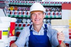 Trabalhador no rolo de pintura de compra do capacete de segurança na loja do agregado familiar Imagens de Stock