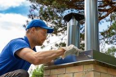 Trabalhador no telhado que instala o tampão da lata na chaminé do tijolo fotos de stock royalty free