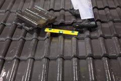 Trabalhador em telhas de telhado da fixação do telhado Foto de Stock