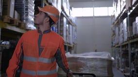 Trabalhador no uniforme que puxa o trole com as caixas entre fileiras das cremalheiras no armazém filme