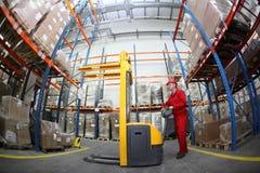 Trabalhador no uniforme vermelho no trabalho no armazém foto de stock