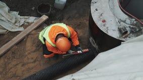 Trabalhador no vedador do uso do capacete de segurança na tubulação plástica no anel concreto da câmara de visita na vala vídeos de arquivo