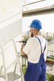 Trabalhador no vestuário do trabalho, em luvas protetoras e em um capacete no local Furando o furo com uma broca na parede Imagens de Stock