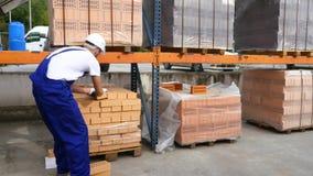 Trabalhador nos tijolos vermelhos da verificação do armazém empilhados em cubos blocos vermelhos de tijolos no estoque Tijolos do filme