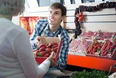 Trabalhador novo do homem do mantimento no mercado local Fotos de Stock Royalty Free