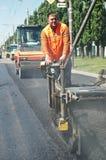 Trabalhador novo do paver na asfaltagem foto de stock