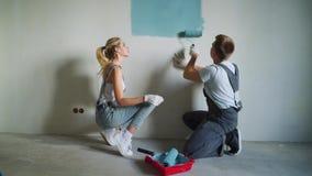 Trabalhador novo dos pares da família que usa o rolo para pintar as paredes no apartamento ou na casa filme