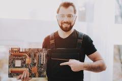 Trabalhador novo ereto com cartão-matriz à disposição foto de stock royalty free