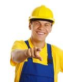 Trabalhador novo feliz que aponta em você e no sorriso Fotografia de Stock