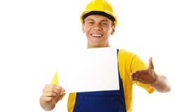 Trabalhador novo feliz que mostra a mensagem e o sorriso em branco Foto de Stock