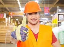 Trabalhador novo profissional com polegares acima na loja Fotografia de Stock Royalty Free
