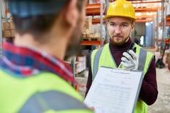 Trabalhador novo que fala ao supervisor no armazém imagem de stock royalty free