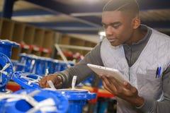 Trabalhador novo que faz o inventário no armazém imagem de stock