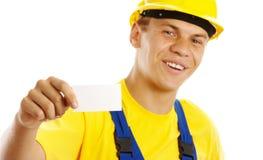 Trabalhador novo que mostra seus cartão e sorriso Imagem de Stock Royalty Free