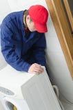 Trabalhador novo que repara a máquina de lavar Fotografia de Stock Royalty Free