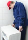 Trabalhador novo que repara a máquina de lavar Fotografia de Stock