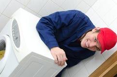 Trabalhador novo que repara a máquina de lavar Foto de Stock Royalty Free