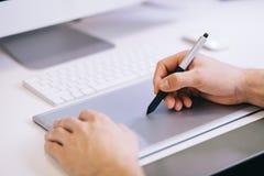 Trabalhador novo que senta-se em um escritório no computador Freelancer em uma camisa azul O desenhista senta-se na frente da jan Imagens de Stock