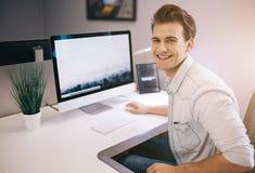 Trabalhador novo que senta-se em um escritório no computador Freelancer em uma camisa branca O desenhista senta-se na frente da j Imagens de Stock